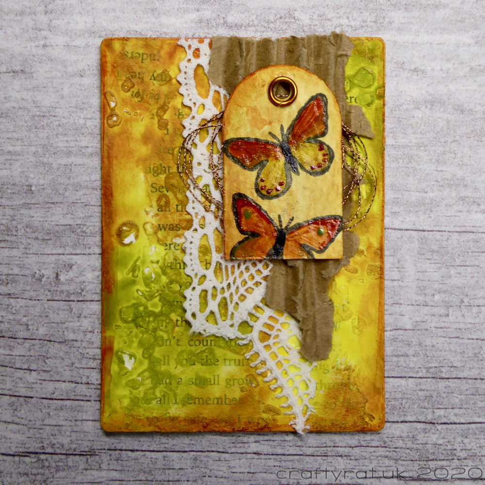 Orange, yellow and green art card with layers of corrugated card, lace and thread topped with a tiny tag with two painted butterflies on it.