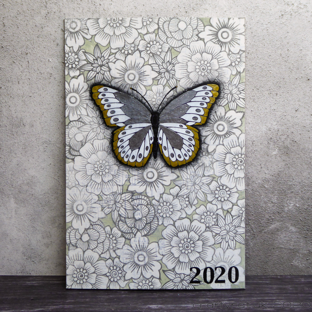 2020 journal cover with a gold, white and chrome butterfly on a background covered with flowers.