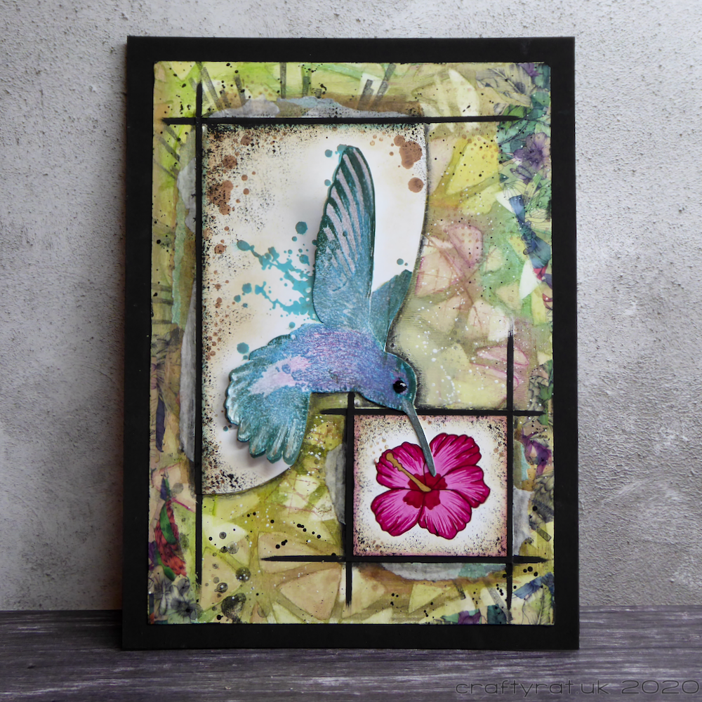 Mixed media piece of a hummingbird and hibiscus flower.