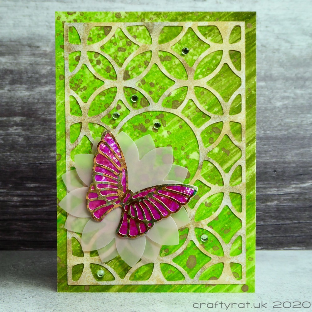A card with a pink butterfly on a vellum flower on a green background topped with a curvy trellis pattern.