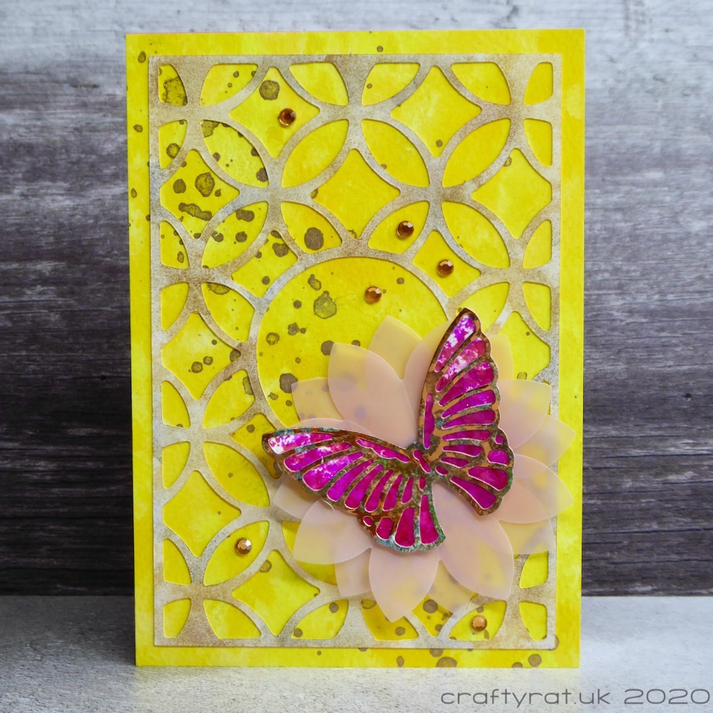 A card with a pink butterfly on a vellum flower on a yellow background topped with a curvy trellis pattern.