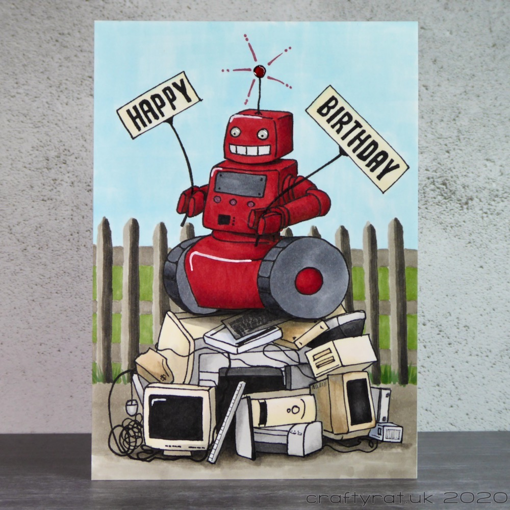 Birthday card with an illustration of a red robot stood on top of a pile of old computer kit in front of a metal fence.