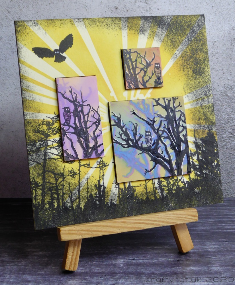 """Forest Owls"" displayed on a small wooden easel."