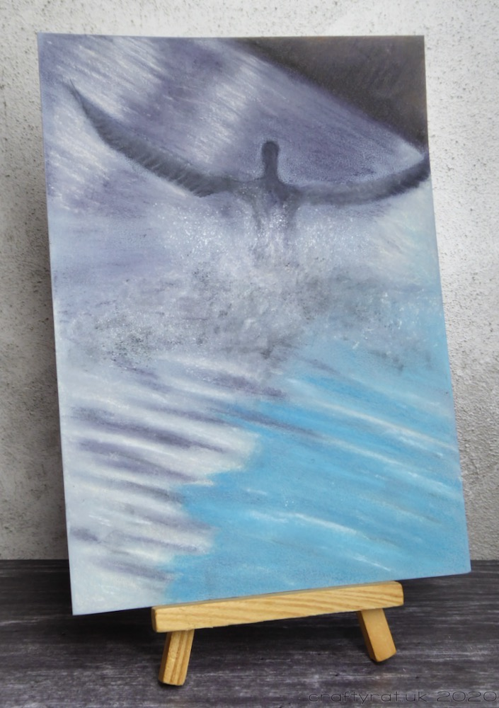 The cormorant drawing displayed on a small wooden easel.