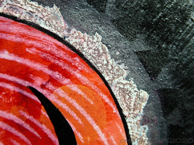 Close-up of the crackle paste edging on the red part of the infinity symbol.