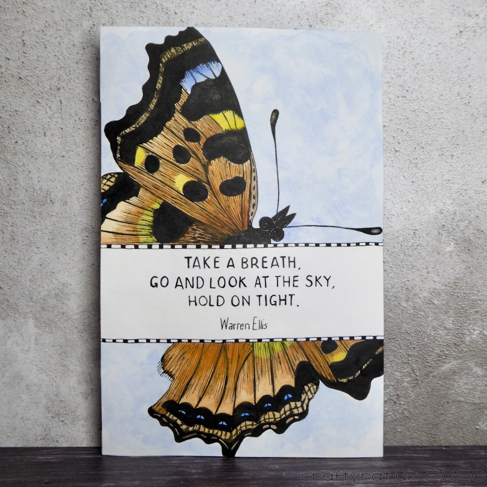"Art journal page with a large butterfly and a banner across it with the quote ""take a breath, go and look at the sky, hold on tight - Warren Ellis""."