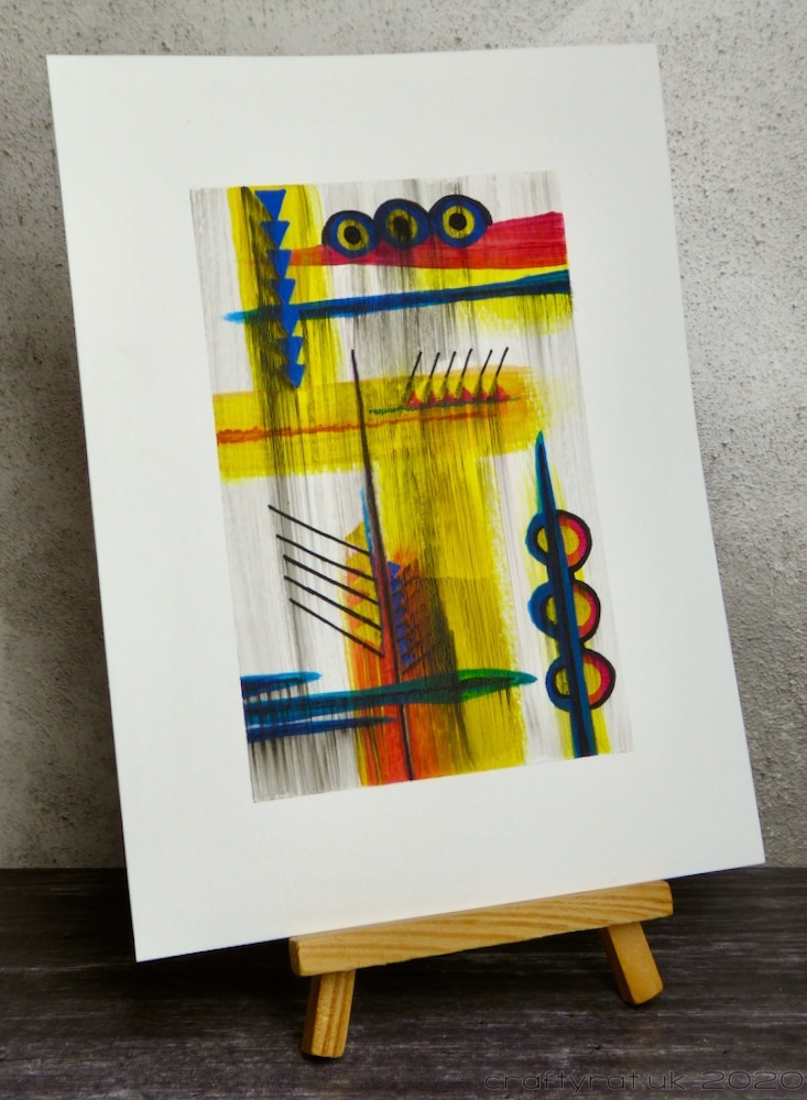 The abstract painting displayed on a mini wooden easel.