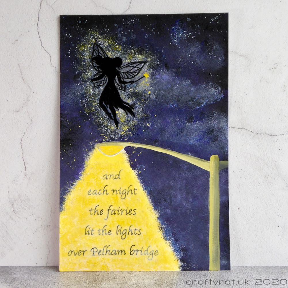 """An art journal page with the silhouette of a fairy above a lit street lamp with the words """"and each night the fairies lit the lights over Pelham bridge"""" in the cone of lamp light."""