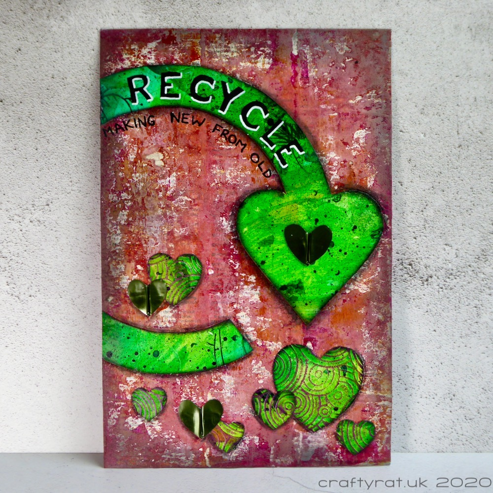 An art journal page with a distressed red background. The main element is a green Recycle Now logo with a scattering of green hearts around it.