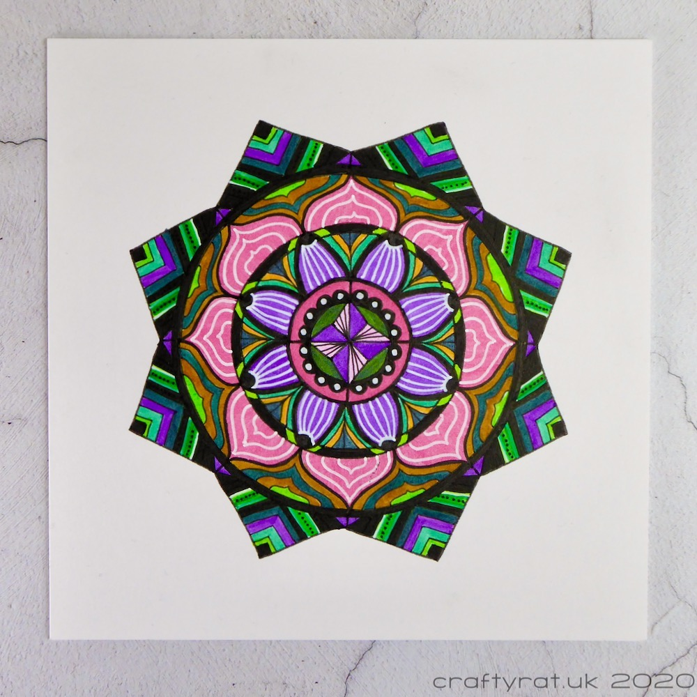 An eight-pointed mandala in purple, pink, green and black.