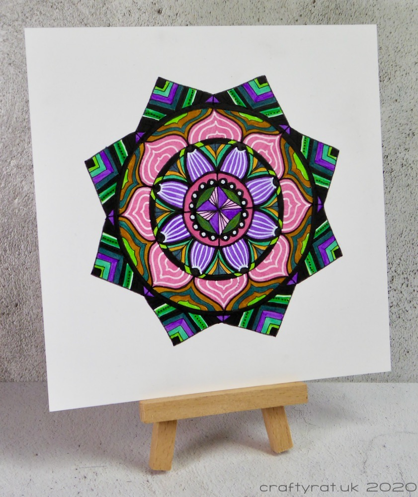 The mandala displayed on a small wooden easel.