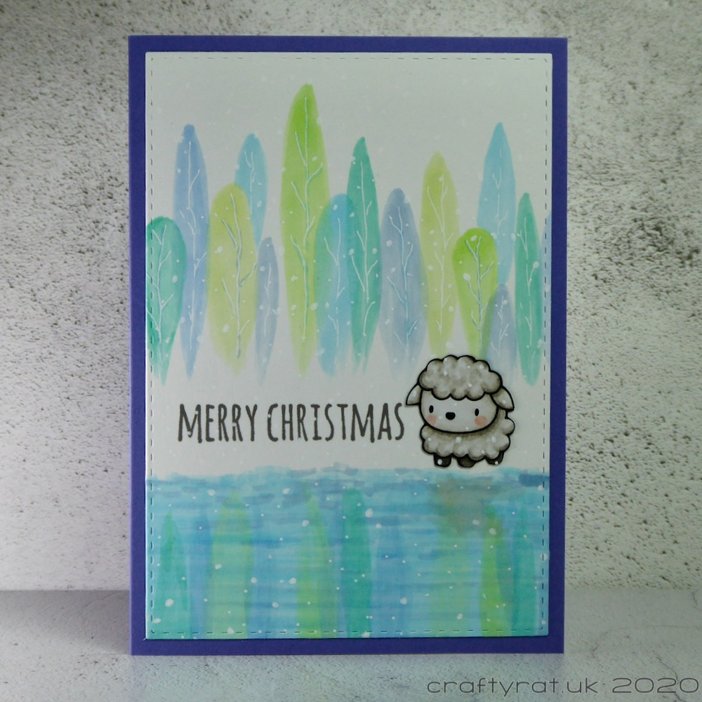 Christmas card with a small sheep standing in front of a blue and green tree line reflected in a lake.
