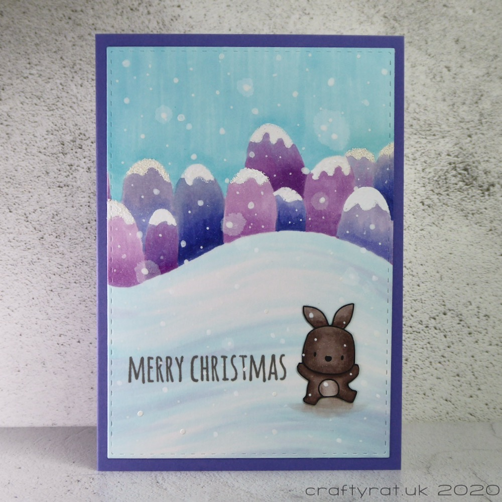 Christmas card with a small bunny sitting on the snow in front of a row of stylised purple hills.