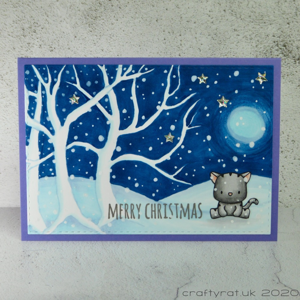 Christmas card with a small cat sitting next to some white trees in front of a night sky.