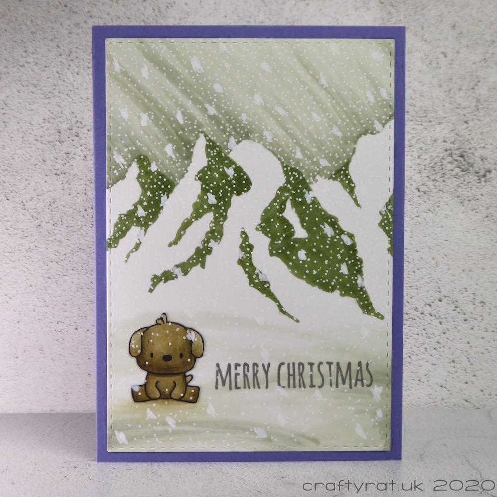 Christmas card with a small dog sitting on the snow in front of a graphic mountain range.