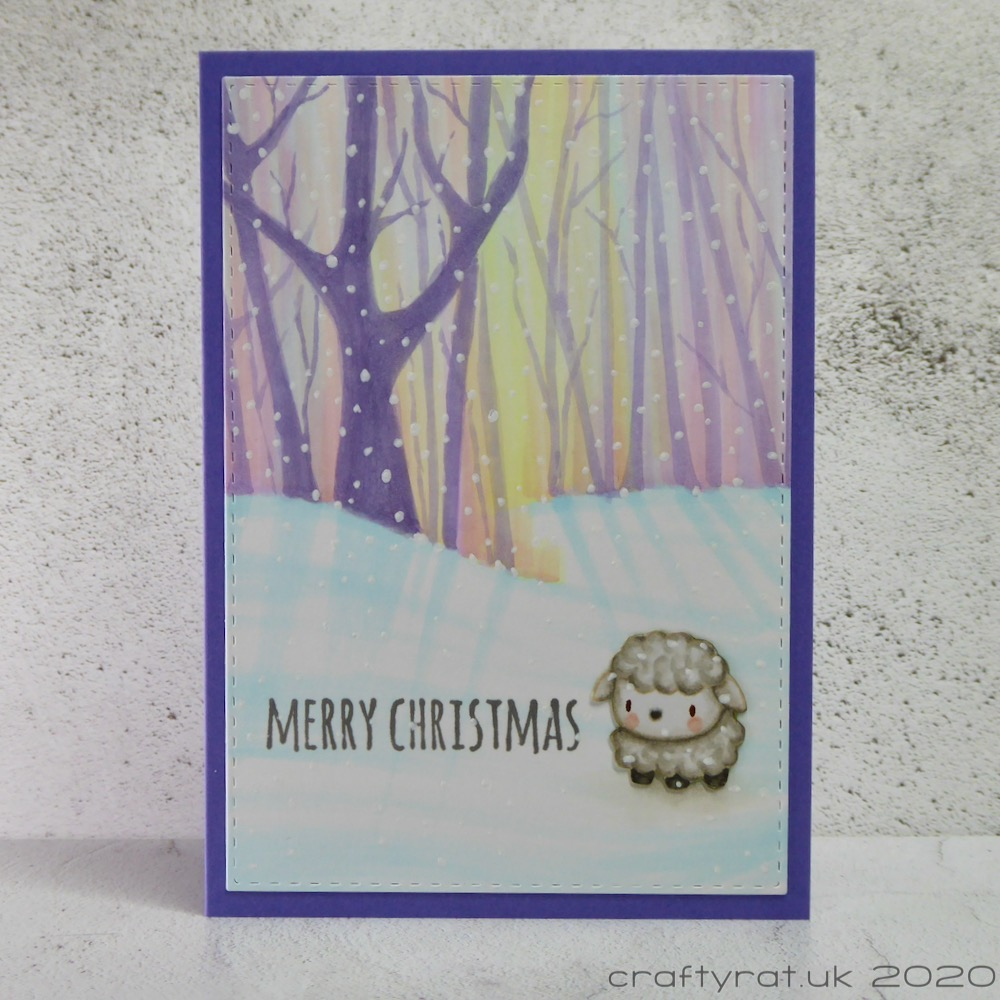 Christmas card with a small sheep sitting on the snow in front of a glowing pinky-purple tree line.