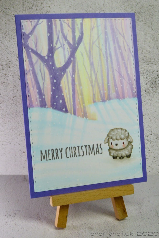 The Christmas card displayed on a small wooden easel.
