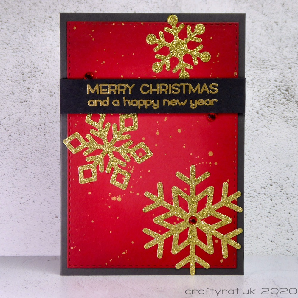 Christmas card with gold glitter snowflakes on a red background with gold splatters.