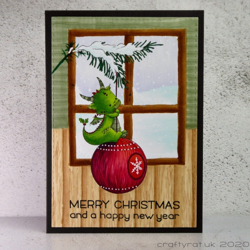 A Christmas card with a little green dragon sitting on a red bauble hanging from a sprig of fir in front of a window.