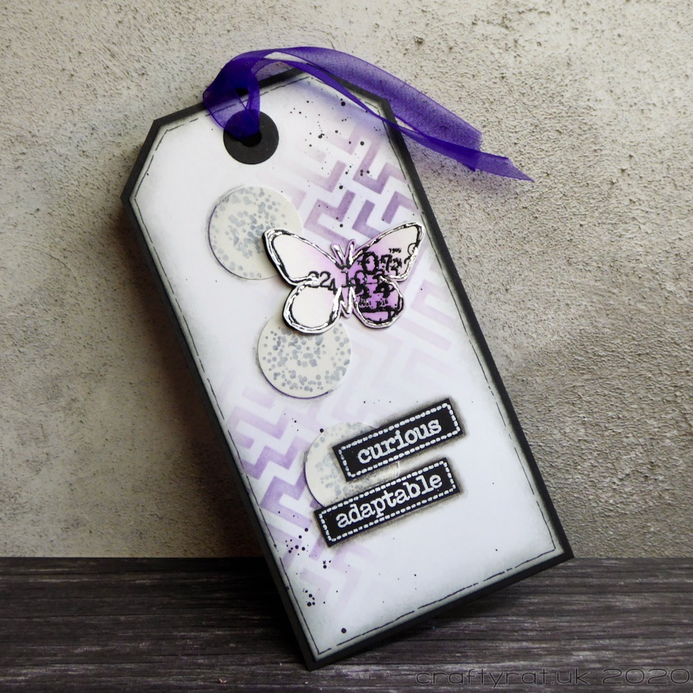 """Large white tag with a purple ribbon. Purple stencilling on the background with a silver-outlined butterfly and the words """"curious"""" and """"adaptable""""."""