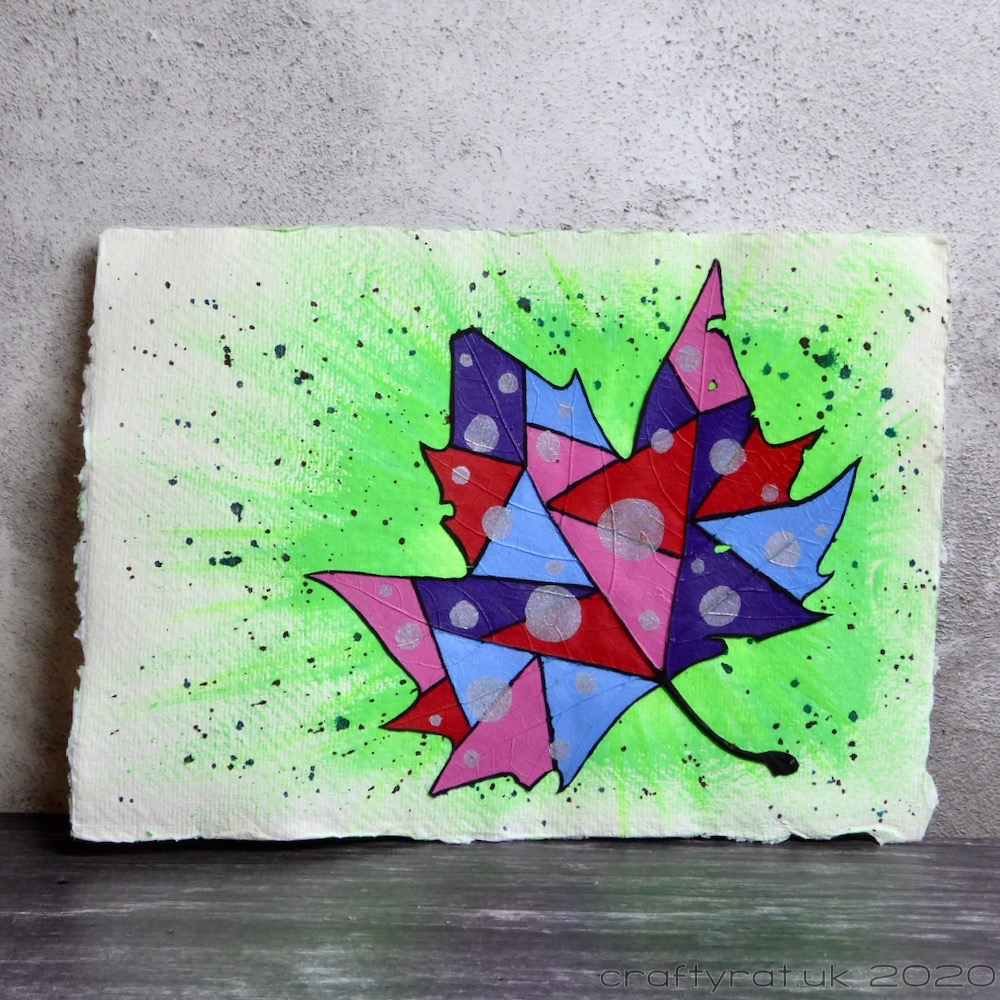 Leaf painted in patchwork of red, pink, blue and purple on a bright green, black splattered background.