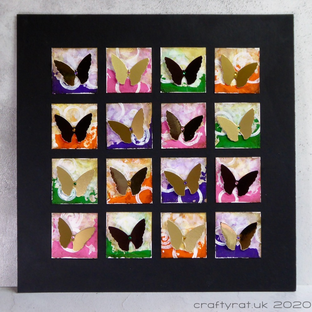 A grid of metallic butterflies on painted squares on a black background.