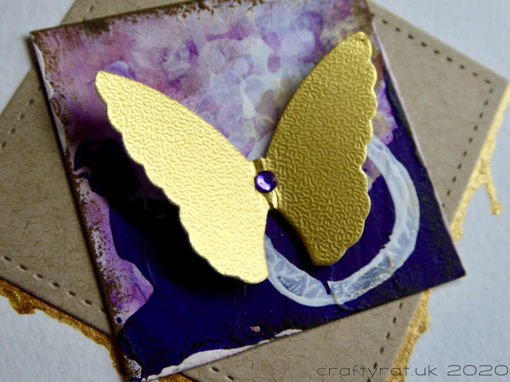 A close-up of the gold butterfly on the purple square.