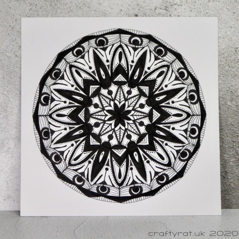 A black and white mandala drawing.