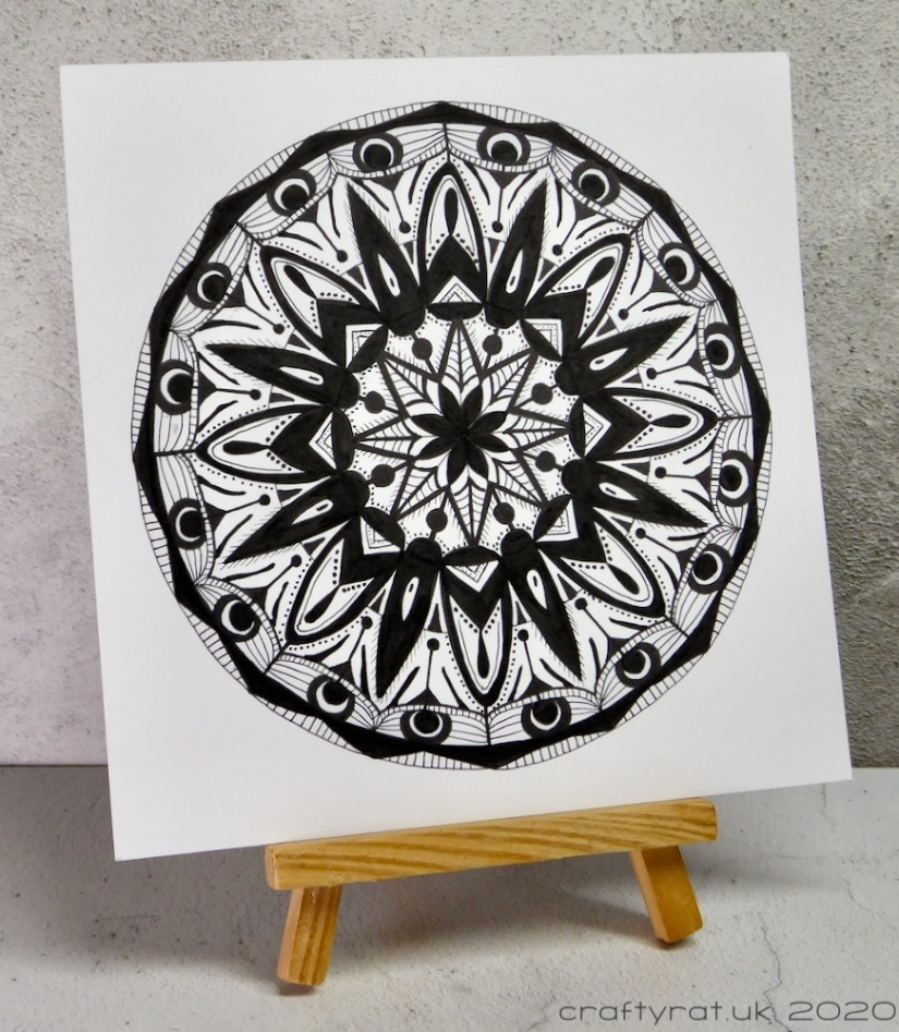 The black and white mandala displayed on a small wooden easel.
