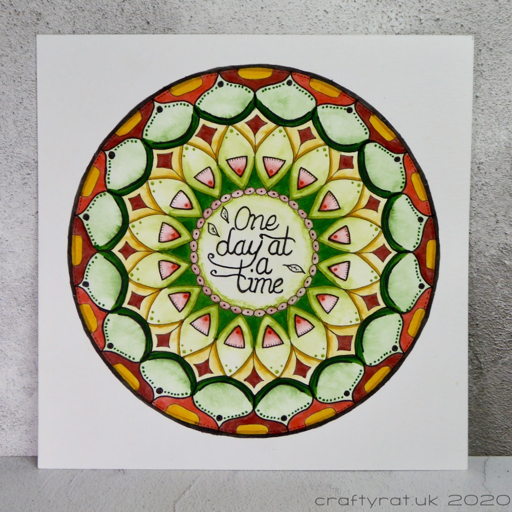 """An autumnal coloured mandala with the phrase """"one day at a time"""" in the centre."""