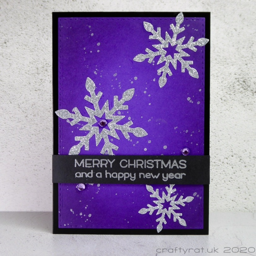 A Christmas card with silver glitter snowflakes on a purple background splattered with silver paint.