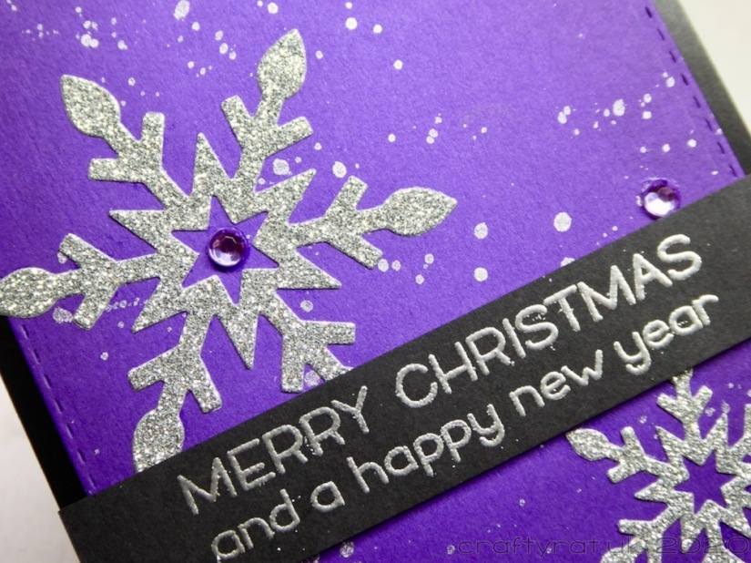 A close-up of the sentiment and one of the snowflakes on the card.