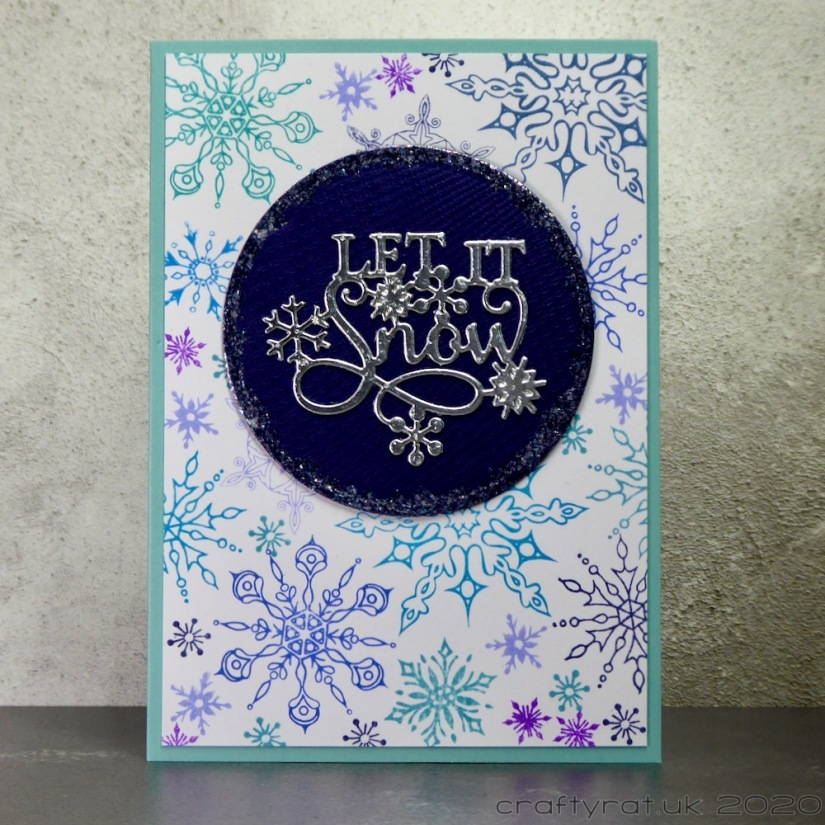 "A Christmas card with a background covered in detailed snowflakes stamped in blues and purples. On top of that is a dark blue circle with a decorative silver die-cut that says ""let it snow""."