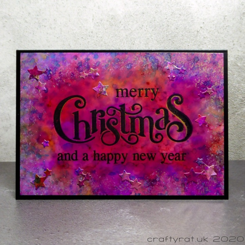 A card that says Merry Christmas and a happy new year on top of a red-purple alcohol ink background with die-cut stars.