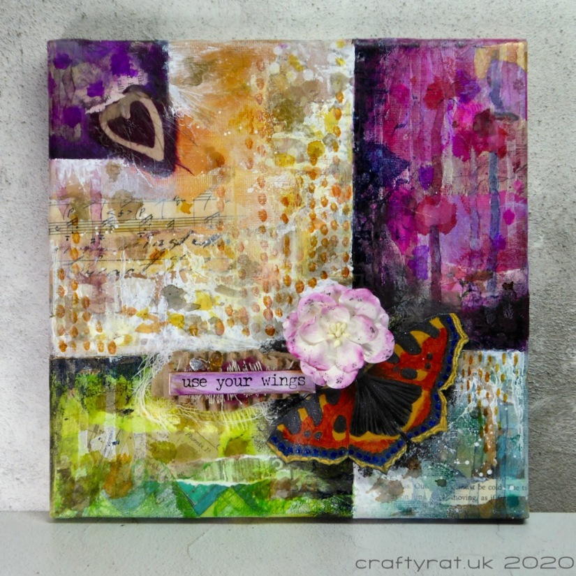 "A mixed media canvas divided into a grid with panels in purples, greens, blues and neutral. It has a focal element comprising a butterfly, flower and the words ""use your wings""."