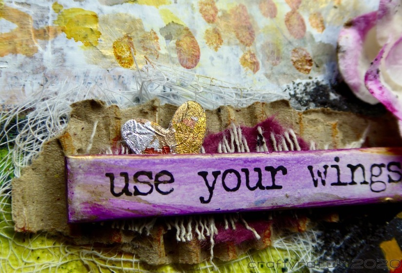 "A close-up of the words ""use your wings"" with a small gilded heart tucked behind them."