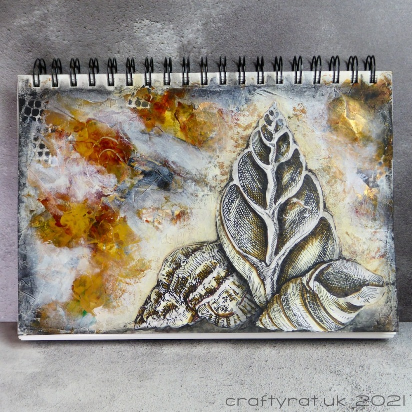 An art journal page with three illustrated shells on a background of neutral colours with touches of gold.