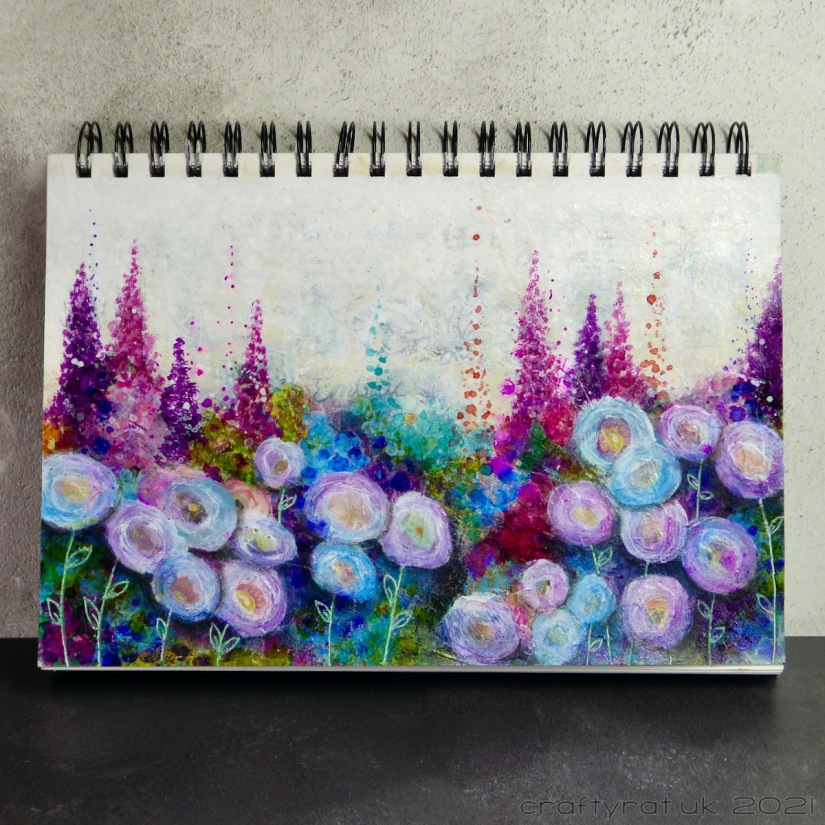 Art journal page with colourful flowers. Round flowers in the foreground and spiky ones at the back.