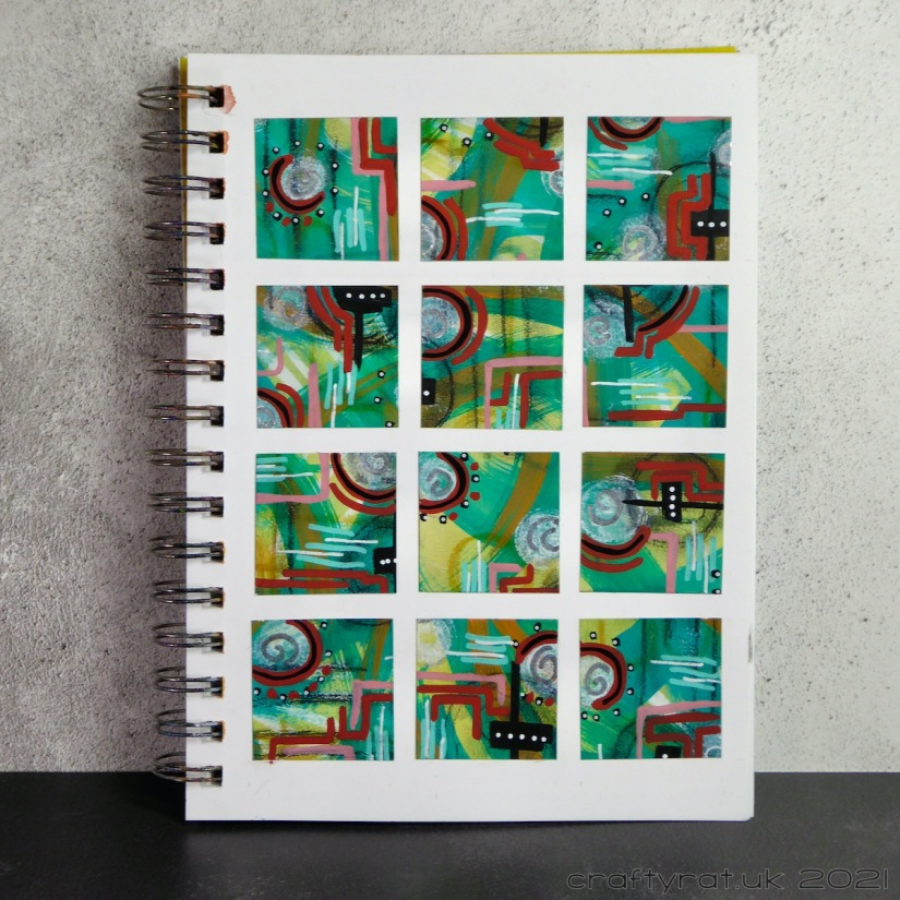 Art journal page with a grid of twelve squares cut from a page of paint swipes and mark-making.