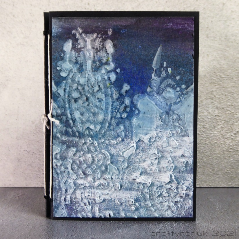 The cover of a small journal, dark blue in colour with white stencilled texture paste over two-thirds of the cover.