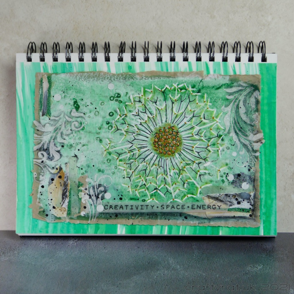 "A predominately green art journal page with a dandelion seed head surrounded by collage, stencilled texture paste and a banner reading ""creativity - space - energy""."