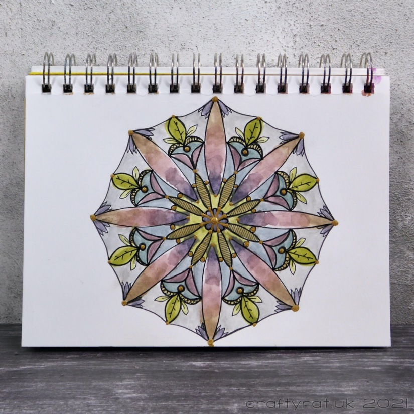 A hand-drawn mandala, loosely painted with muted purple, pink, blue and green.